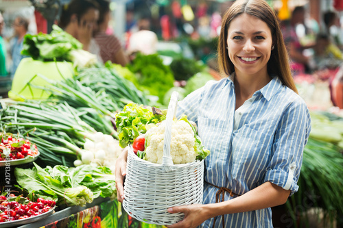 Foto Murales Young woman buying vegetables at the market.