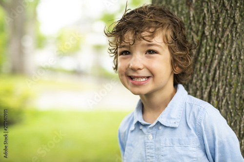 Foto Murales Cute Caucasian boy happily close to a tree