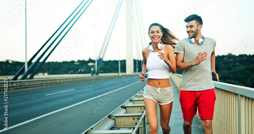 Foto Spatwand Hardlopen Attractive man and beautiful woman jogging together