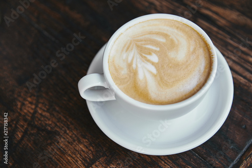 cup of fresh coffee with latte art on rustic wooden table