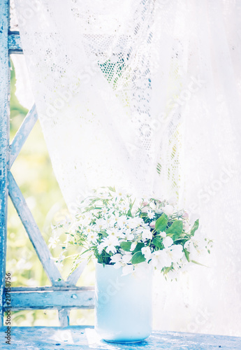 Foto Murales Delicate white forest flowers in a blue cup on an old window overlooking the sunny garden. Retro vintage style. Gentle joyful mood.