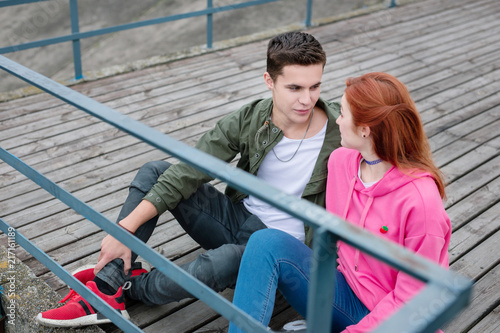 Foto Murales Pleasant communication. Nice joyful couple talking to each other while sitting on the dock