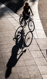 Paris, France - October 2014:  Deep shadows in the late-afternoon from a woman riding a bicycle in Paris