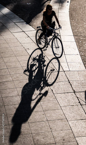 Wall mural Paris, France - October 2014:  Deep shadows in the late-afternoon from a woman riding a bicycle in Paris