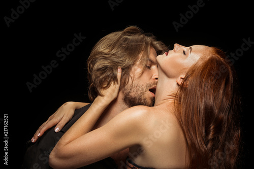 Leinwanddruck Bild Real passion. Beautiful young loving couple bonding to each other while both standing against black background. Passion, couple, love, sensuality, erotic, sex, relationship concept