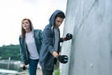 Street art. Nice creative man drawing graffiti while standing together with his girlfriend - 217164184