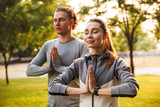 Fitness loving couple friends in park make meditate exercises.