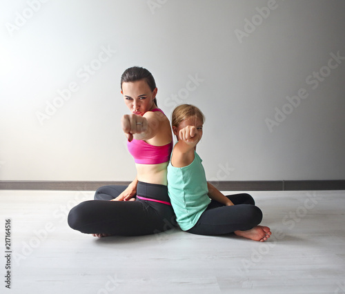 Poster Young woman having fun with kid after yoga