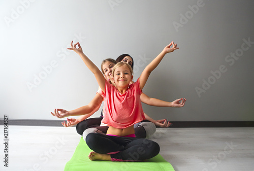 Leinwanddruck Bild Young woman having fun with kids doing yoga