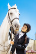 Long braid. Dark-haired female rider with long braid feeling very cheerful while preparing for horse riding