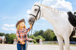 Beauty of horse. Cheerful blonde-haired girl wearing jeans and cowboy hat feeling amused by beauty of horse