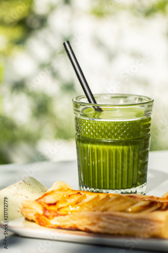 Canvas Sap Green detox juice glass with an apple pie in a sunny outdoors