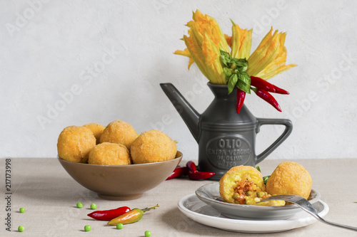 Italian still life with arancini and flowers of pumpkins. Arancini - italian rice balls which are coated with bread crumbs and then deep fried, filled with ragu (meat and tomato sauce) and peas. - 217173998