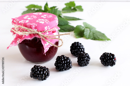 Foto Murales Jar of blackberry jam on white wooden background. . Delicious fruit . Blurred background.Food and healthy concept.