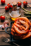 Rustic wooden table wiht prawns and some ingredients for seasoning and vegetables to mix them - 217194104