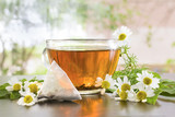 A transparent mug with tea on the table. Flowers of white daisy. Light background