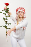 Woman in winter furry hat holding red rose - 217202377