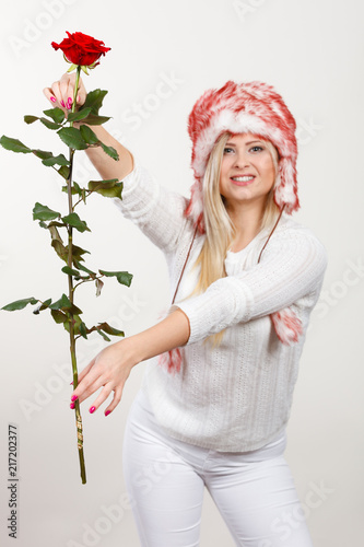 Foto Murales Woman in winter furry hat holding red rose