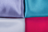 Background of colorful fabrics red green pearl and purple.