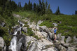 A young woman is hiking near a waterfall in Mt. Rainier National Park.