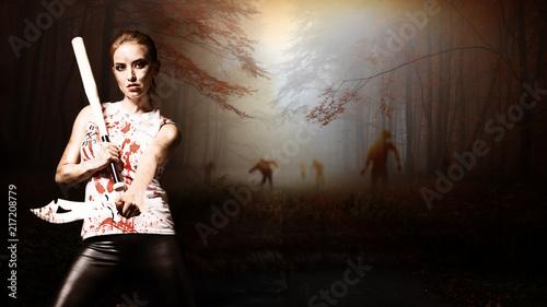 Leinwanddruck Bild Frau mit Machete und Baseballschläger vor schaurigem Wald mit Zombies