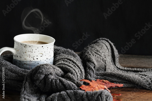 Hot steaming cup of coffee with cream wrapped in a cozy grey scarf with fallen leaves for autumn. Extreme shallow depth of field with selective focus on mug of coffee.