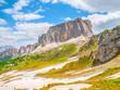 Quadro Lastoni de Formin, aka Ponta Lastoi de Formin. Giant mountain block with blooing meadow and summer sky, Dolomites, Italy.