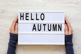 Female hands hold modern board with text 'Hello Autumn' over white wooden surface, top view. Overhead, flat lay, from above.