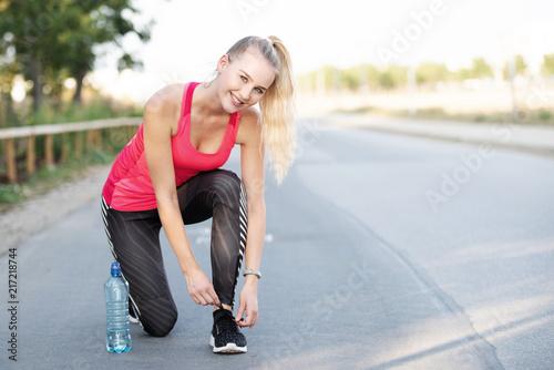 Foto Murales Sportliche junge Frau bindet ihre Laufschuhe