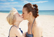 Quadro modern mother and daughter in swimsuit on seacoast kissing