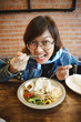 Girl Eating pork fried rice In Restaurant