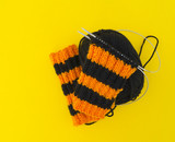 The process of knitting gaiters on a Halloween holiday. Witch costume.