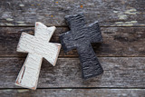 Black and white cross on wooden background