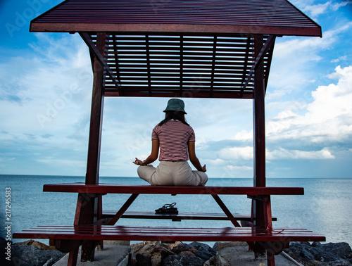 Obraz na płótnie She is meditating and yoga on the small saloon by the sea.
