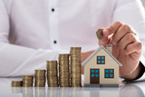 Businessman holding coin over house model - 217258997