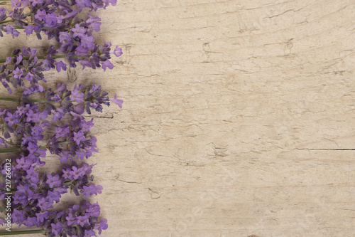 Lavender flowers on the left side on a scaffolding wooden background seen from an high angle