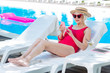 Leinwanddruck Bild - Deck chair. Modern grandmother wearing bright red swimming suit lying on deck chair near outside pool