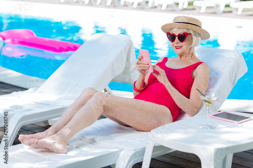 Leinwanddruck Bild Deck chair. Modern grandmother wearing bright red swimming suit lying on deck chair near outside pool