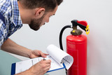 Man Checking Fire Extinguisher Writing On Document