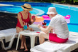 Playing cards. Modern pensioners feeling entertained while playing cards while sitting near the pool