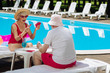 Leinwanddruck Bild - Winning game. Blonde-haired retired woman feeling happy winning card game while playing with husband near pool