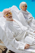 Leinwandbild Motiv Eye patches. Pensioners wearing eye patches and white bathrobes lying near pool enjoying peaceful atmosphere