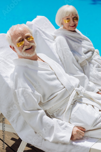 Leinwanddruck Bild Eye patches. Pensioners wearing eye patches and white bathrobes lying near pool enjoying peaceful atmosphere
