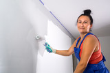 Woman at painting a room with paint roller - 217271332