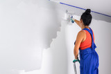 Woman at painting a room with paint roller - 217271343