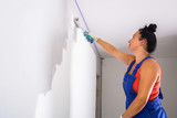Woman at painting a room with paint roller - 217271366