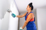 Woman at painting a room with paint roller - 217271381