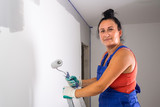 Woman at painting a room with paint roller - 217271395