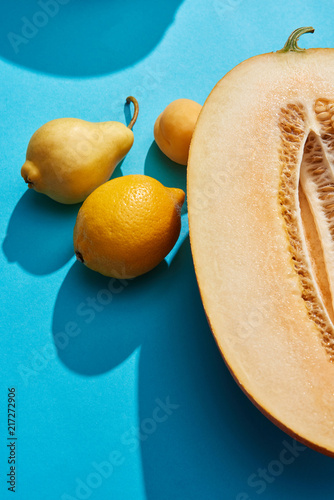 Foto Murales close-up view of fresh ripe melon, pear, apricot and lemon on blue