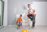 Couple painting a room with paint rollers - 217275538